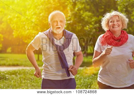 Two active happy seniors running in nature in summer