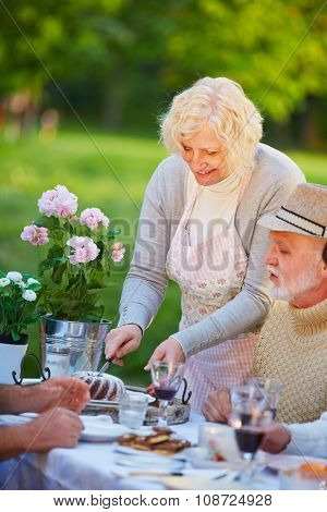Senior woman serving ring cake at birthday party in a garden