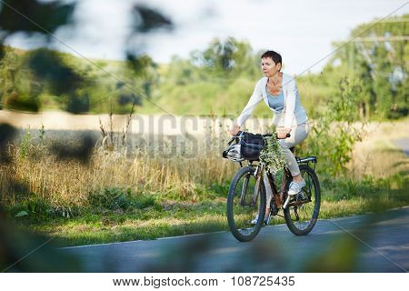 Old woman riding her bike on a street in summer