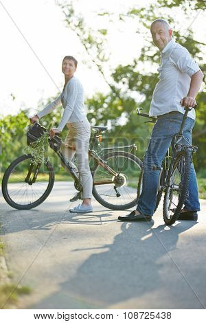 Happy senior couple taking bike trip in summer with bicycles