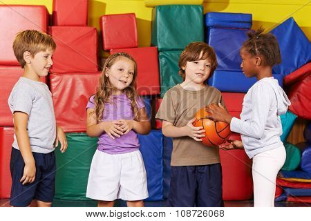 Children playing together with a ball in gym of kindergarten
