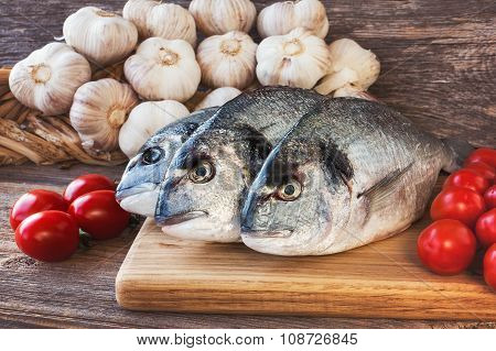 Fresh Dorada Fish On Wooden Cutting Board With Vegetables. Toned