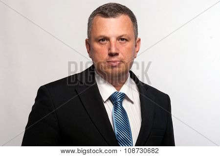 Confidential middle-aged man in a dark suit and tie seriously is looking straight into eyes.