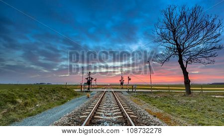 Railroad Crossing In Open Rural Countryside Under Stunning Sky