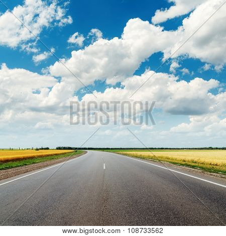 asphalt road to horizon and cloudy sky