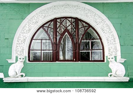 Arched window with sculptures of cats