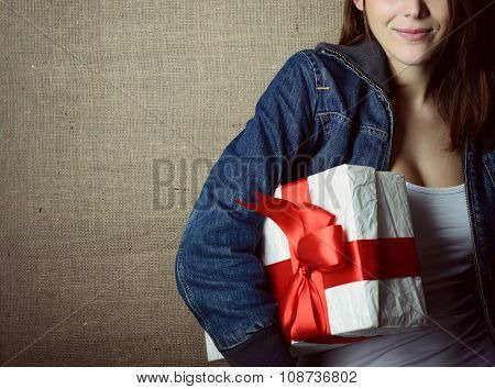Portrait of attractive cheerful girl in sleeveless sports white shirt holding gift box with red bow over canvas background, toned and noise added