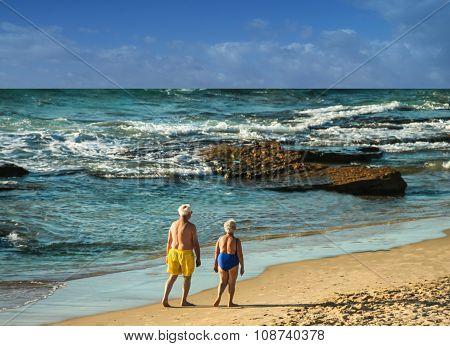 Elderly Couple Makes An Evening Walking Along The Seashore
