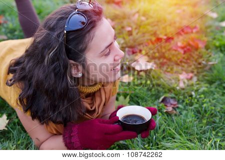 Female Drinking Cup Of Coffee In Nature