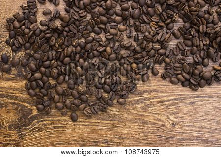 Whole aromatic coffee beans on a wooden background closeup