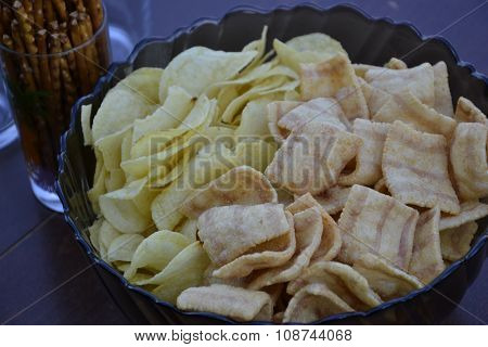 Close up of heap of ripple potato crisp with bacon and ham flavor. Chips in bowl on the table