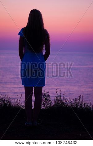 Girl stands on a sea beach