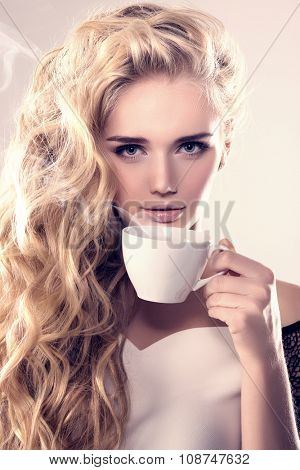 Model with coffee cup, mug in coffee shop. Fashion Woman, tea party time. Blonde girl, tea set