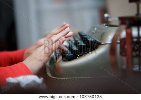 Hands of a man typing on typewriter