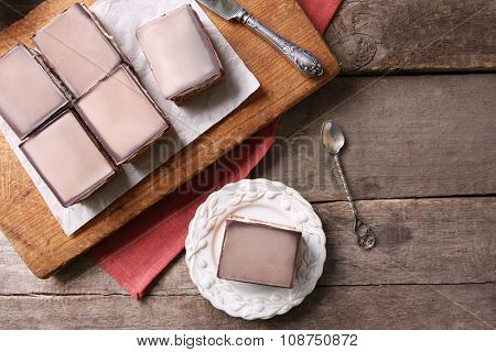 Delicious chocolate brownies on plate, on wooden background