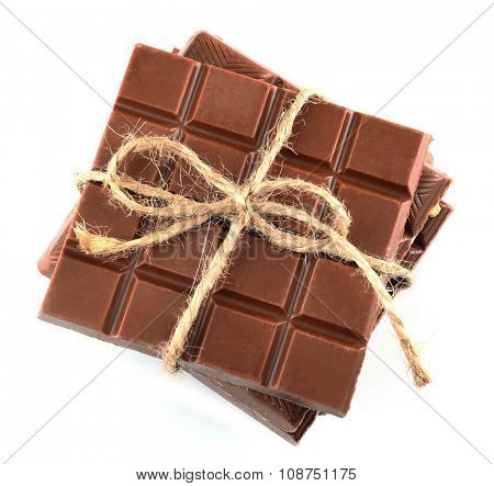 Milk chocolate bar with bow on color wooden background