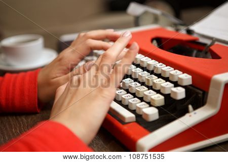 human hands writing on red typewriter