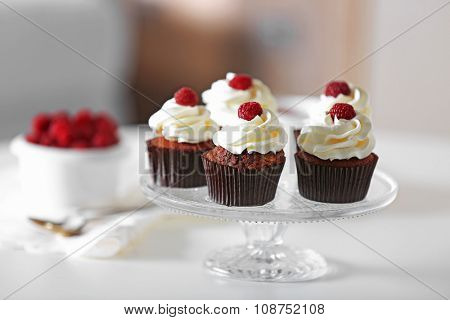 Beautiful chocolate cupcakes with cream and raspberry on table