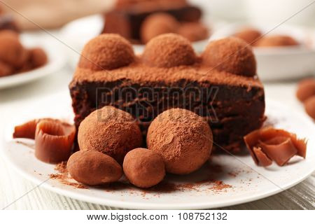 Slices of chocolate cake with a truffle on plate closeup