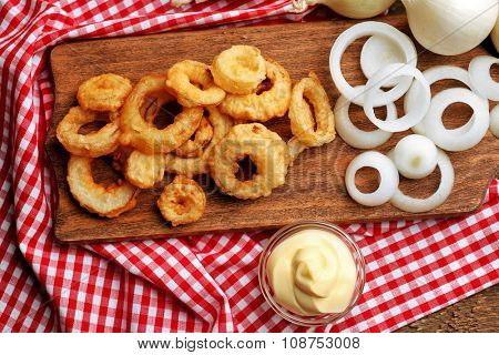 Chips rings with sauce and onion on cutting board