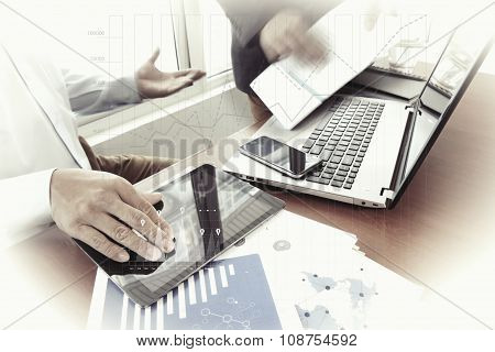 Business Documents On Office Table With Smart Phone And Digital Tablet And Stylus And Two Colleagues