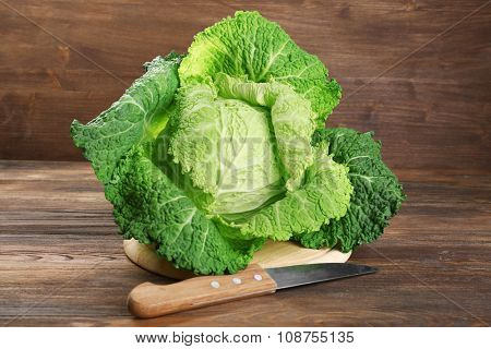 Savoy cabbage on cutting board on wooden background