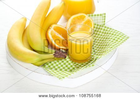 Bananas, oranges and juice on green checkered napkin