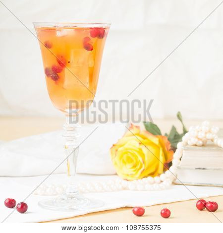 Glass Of Cranberry Cocktail With Vintage Books And Pearls