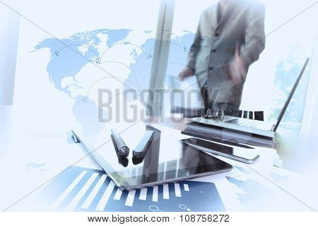 Business Documents On Office Table With Smart Phone And Digital Tablet And Man Working In The Backgr