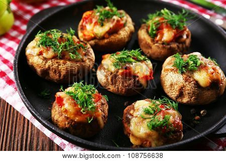 A frying pan with stuffed mushrooms on the table