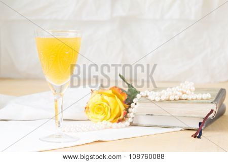 Glass Of Mimosa Cocktail With Vintage Books And Pearls