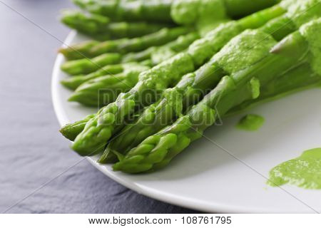 Fresh asparagus dish in green sauce on the table, close up