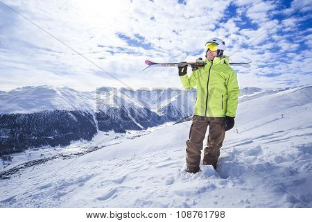 Sporty men with skis in a snow mountain resort