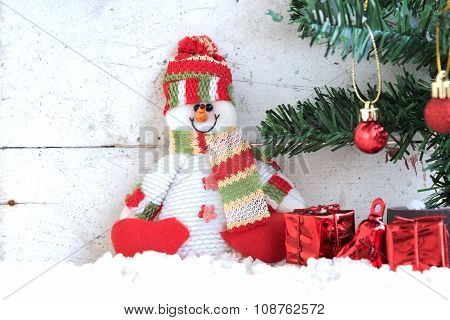 Snowman Sitting On The Snow With Christmas Tree In Vintage Background