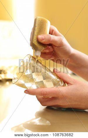 Woman decorates glass candlestick