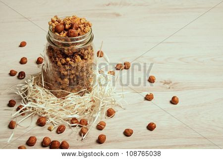 Healthy Muesli In Jar With Crispy Nuts On Wooden Table