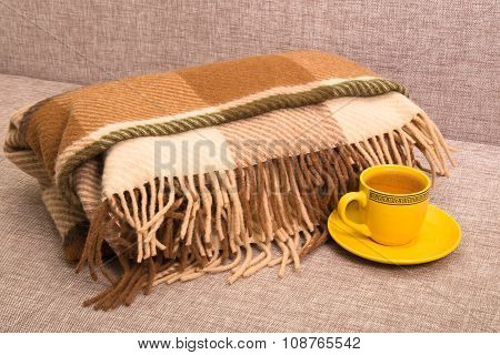 Checkered Woolen Plaid And Yellow Cup With Tea On A Sofa