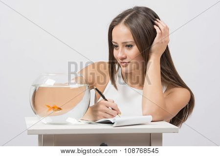 Girl Writing In A Notebook And Looking At A Goldfish In An Aquarium