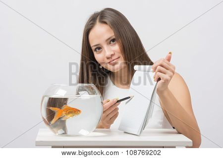 Girl Shows A Pen In A Notebook Record Gold Fish In The Aquarium