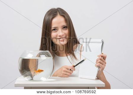 Girl Shows A Pen Entry Pad, Standing Next To An Aquarium With Goldfish