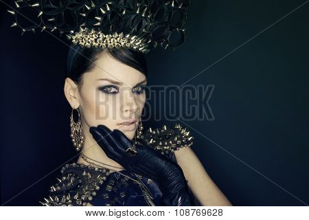 Woman in blue dress and headwear with spikes