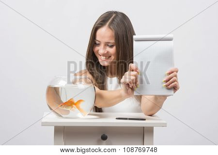 Girl Shows A Notebook With A Record, Standing Next To An Aquarium With Goldfish