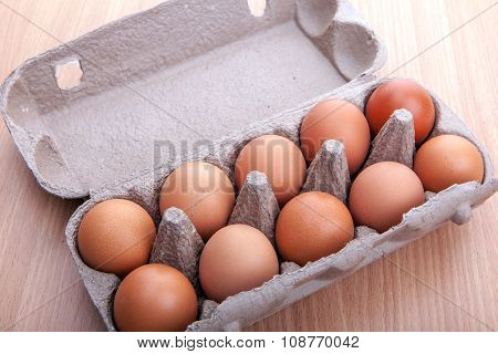 Brown Eggs In Egg Carton On Kitchen Table