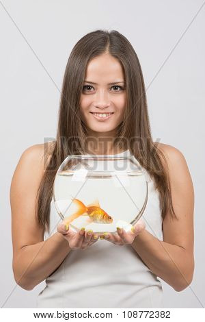 Portrait Of A Happy Young Girl With An Aquarium With Goldfish In Hands