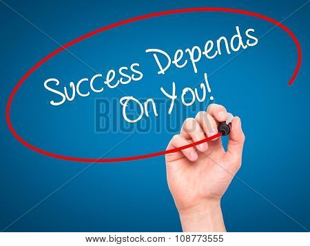 Man Hand writing Success Depends On You! with black marker on visual screen.