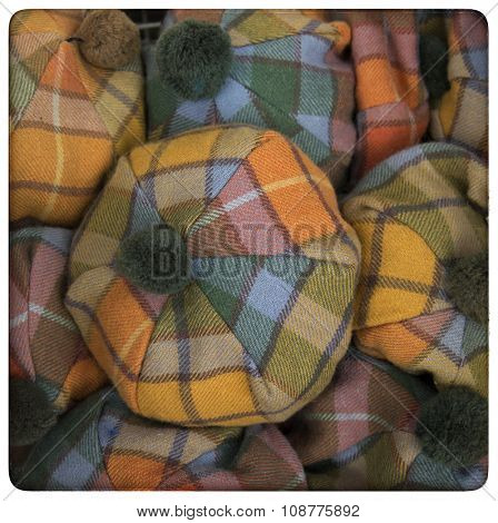 Yellow, orange and blue scottish tartan hats.  Processed to look like an aged, instant photo.