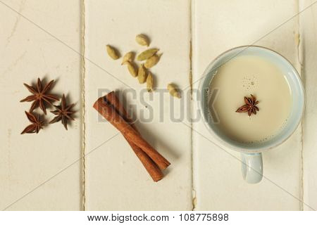 Top view of a chai tea with cinnamon, anise and cardamom on a wooden background