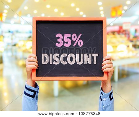 35% Discount Message On Blackboard With Hand Holding.