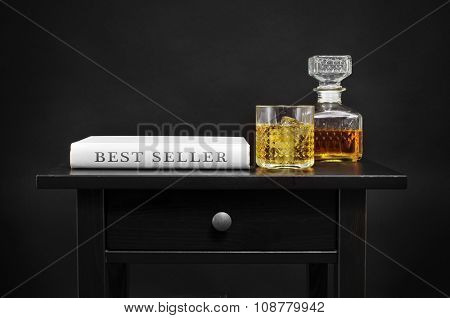 a book with the text best seller written in its spine, and a bottle and a lowball glass with liquor on a black table, over a black background