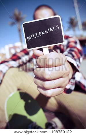 a young caucasian skater outdoors shows a signboard with the text millennials written in it